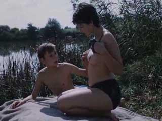 Женщина дает потрогать и обсуждает с мальчиком свою грудь.