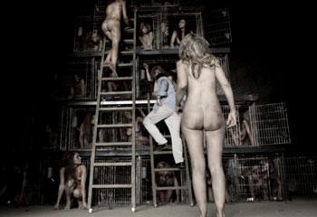 Голые женщины-рабыни заперты в клетках для любовных утех.