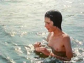 Молодая девушка плавает топлес в море